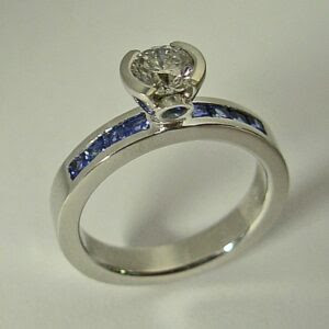 14 Karat White Gold Engagement Ring with Diamond and Sapphire - Materials: 14 karat white Gold Engagement Ring with a custom semi bezel head for a 3/4 carat round Diamond. (Style is good almost any size Diamond) Two bezel set round Sapphires are set on each side of the custom head. On Each side of the ring are 4 channel set princess cut Celon Sapphires, 8 total. The ring is priced for the mounting only. Diamond prices are available by request.