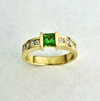 14 karat gold ring with 8 Princess Cut Diamonds Channel set and a Princess Cut Tsavorite Center Stone.
